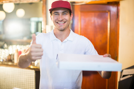 fast food restaurant: Pizza delivery man holding pizza box gesturing thumbs up in restaurant