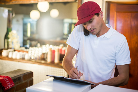 over the counter: Pizza delivery man taking an order over the phone at counter in restaurant