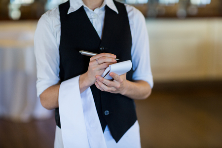 order in: Mid section of waitress taking order in restaurant Stock Photo