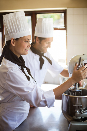 blending: Chef in commercial kitchen blending the batter in mixing blender Stock Photo
