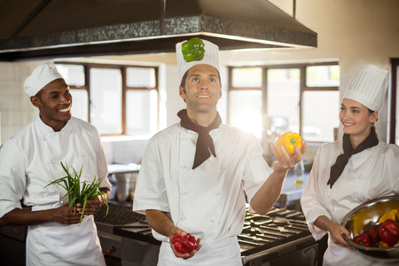 commercial kitchen: Chefs playing with vegetables in commercial kitchen