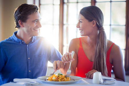 eating pasta: Young couple talking while having lunch in a restaurant