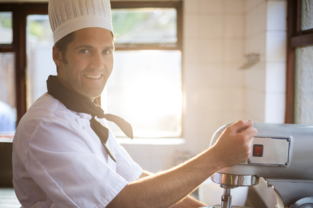 blending: Portrait of chef in commercial kitchen blending the batter in mixing blender Stock Photo