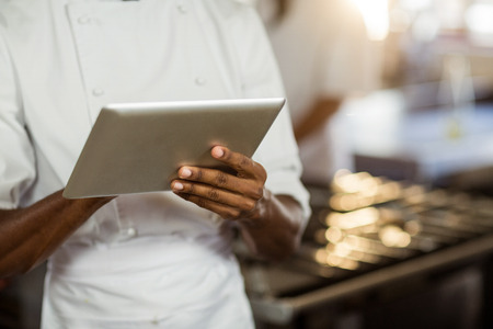 commercial kitchen: Mid section of chef using digital tablet in commercial kitchen Stock Photo
