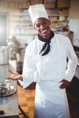 Portrait of smiling chef standing in commercial kitchen