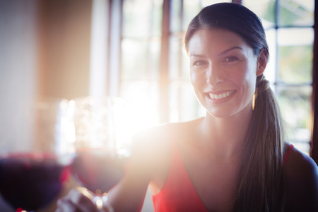 romance strategies: Portrait of happy young woman toasting wine glass in a restaurant