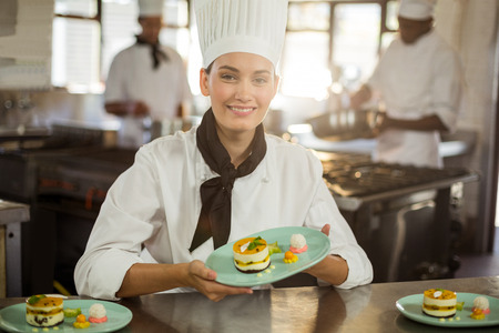 commercial kitchen: Portrait of female chef holding dessert plate in commercial kitchen