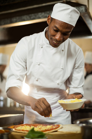sprinkling: Chef sprinkling cheese on a pizza in commercial kitchen