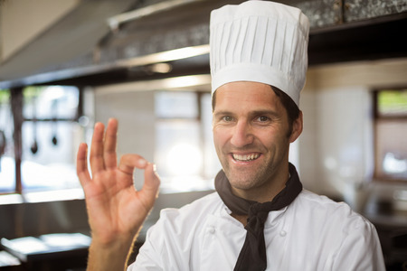 commercial kitchen: Portrait of happy chef making ok sign in commercial kitchen