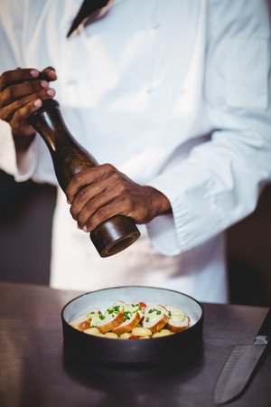 sprinkling: Mid section of chef sprinkling pepper on a salad in commercial kitchen