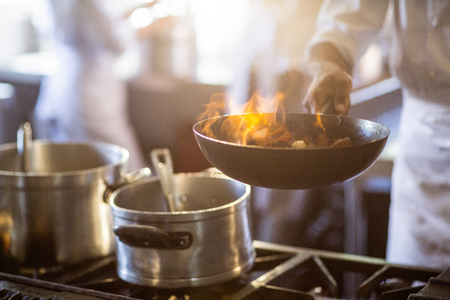 commercial kitchen: Chef tossing stir fry over large flame in commercial kitchen