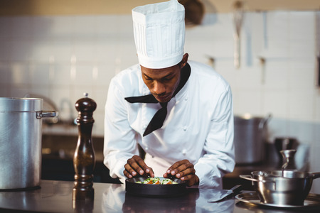 commercial kitchen: Chef preparing a salad in commercial kitchen Stock Photo
