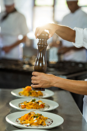 sprinkling: Chef sprinkling pepper on a meal in commercial kitchen