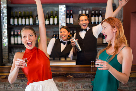 bar counter: Happy women having tequila at bar counter