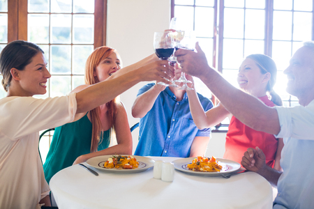 toasting wine: Friends toasting wine glass while having meal at restaurant Stock Photo