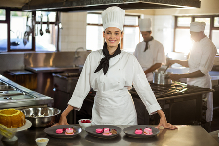 Portrait of smiling female chef presenting dessert plates in commercial kitchen