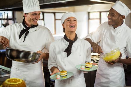 commercial kitchen: Chefs preparing a dessert in commercial kitchen Stock Photo