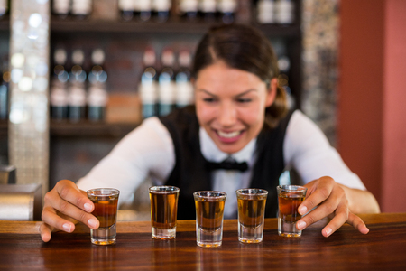 by placing: Bartender placing shot glasses in a row on bar counter in bar Stock Photo
