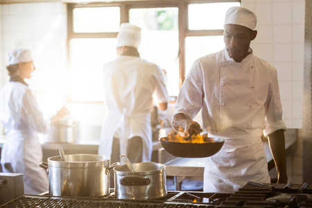 tossing: Chef tossing stir fry over large flame in commercial kitchen