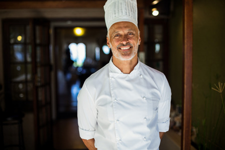 hands behind back: Portrait of chef standing with hands behind back in restaurant Stock Photo