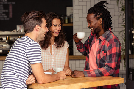 thirties: Friends talking together and smiling in cafeteria Stock Photo