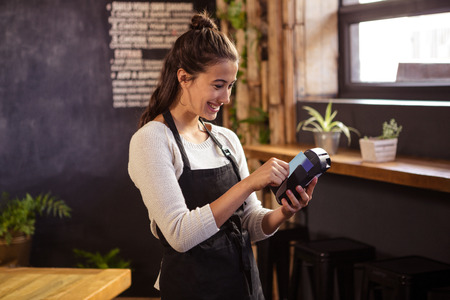 reader: Smiling waitress using a bank card reader in cafeteria Stock Photo