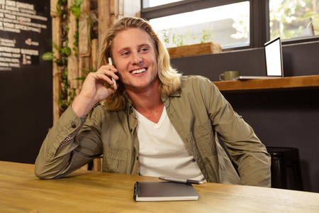 man long hair: Happy man using his smartphone in a cafeteria