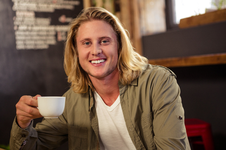 man long hair: Happy man holding a cup of coffee in a cafeteria