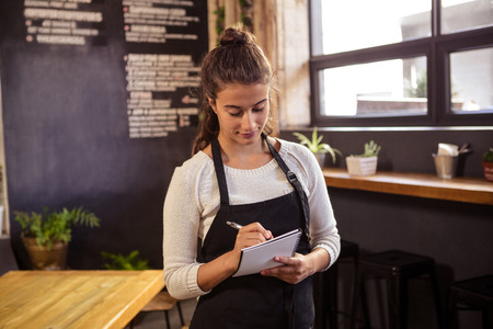 order in: Beautiful waitress taking order in cafeteria Stock Photo