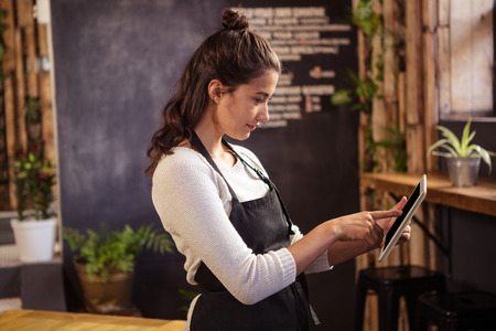 cafeteria: Beautiful waitress using digital tablet in cafeteria