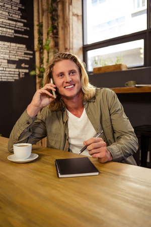 phoning: Happy man using his smartphone in a cafeteria