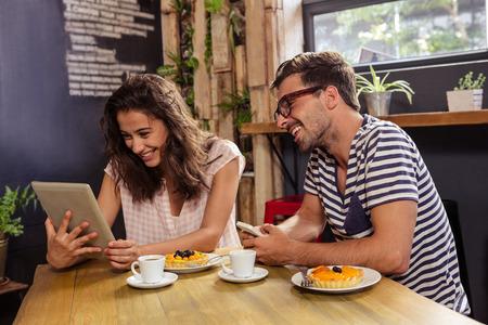 tomando refresco: Pareja joven sentado en la mesa que usa la tableta digital en la cafeter�a
