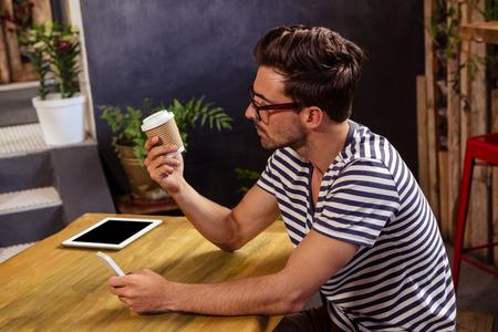 hombre tomando cafe: Joven sentado en la mesa mirando vaso desechable en la cafetería Foto de archivo