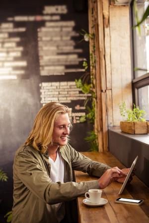 tomando refresco: Feliz joven sentado en la mesa que usa la tableta digital en la cafetería