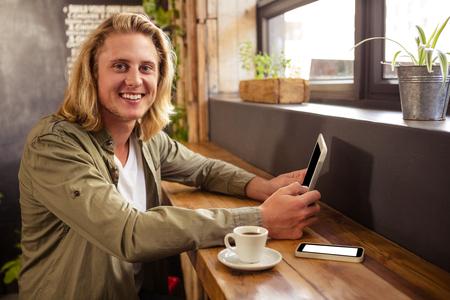 tomando refresco: Retrato de hombre joven feliz sentado en la mesa que usa la tableta digital en la cafetería Foto de archivo