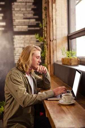strong chin: Young man sitting at table using laptop in cafeteria Stock Photo