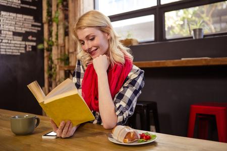 tomando refresco: Hermosa mujer joven sentada en la mesa de lectura de la novela en la cafetería