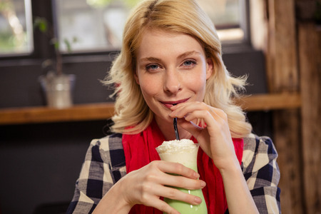 tomando refresco: Portrait of beautiful young woman drinking mocktail in cafeteria