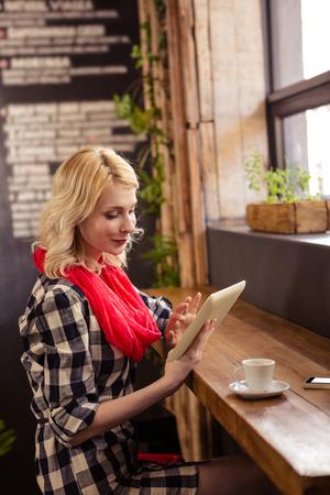 tomando refresco: Hermosa mujer joven sentado en la mesa que usa la tableta digital en la cafeter�a