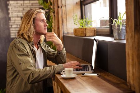 tomando refresco: joven serio sentado en la mesa con ordenador portátil en la cafetería
