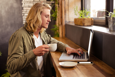 tomando refresco: Young man using laptop while having coffee in cafeteria