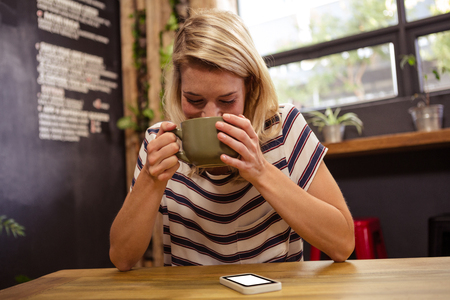 hot beverage: Woman drinking a hot beverage in the cafe Stock Photo