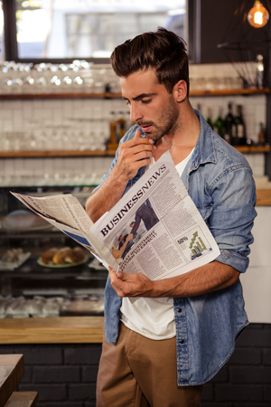 strong chin: Man reading the newspaper in a cafe
