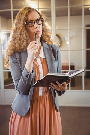 well dressed woman: Business woman holding a book at work
