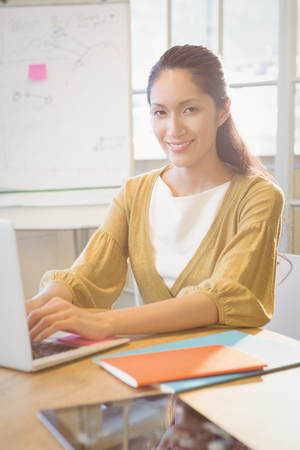 well dressed woman: Businesswoman posing on her desk at work Stock Photo
