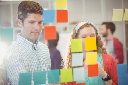 Business people looking at post it on the wall in office