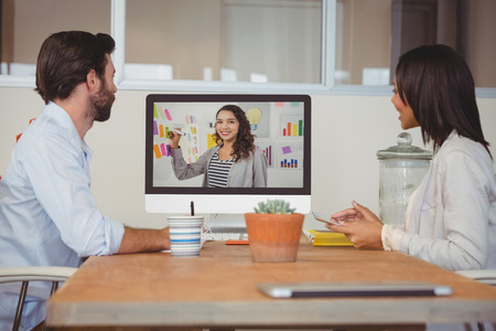 video conference: Two colleagues having a video conference in office