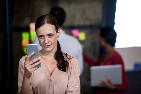focus on the foreground: Focus on foreground of woman looking her mobile phone in the office Stock Photo