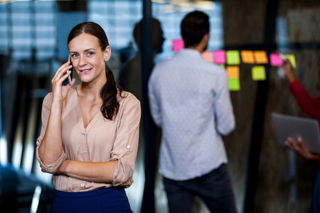 focus in foreground: Focus on foreground of businesswoman calling in the office