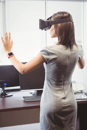 well dressed woman: Business woman using 3D glasses in office Stock Photo